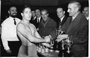 El president de lluita, Sr. Emilio López Jimeno, lliura el trofeu de Campió: a Marià Cortés al febrer de 1960 al Saló Iris de Barcelona participant també un nodrit grup de lluitadors de tots els pesos pertanyents al Barcelonès.