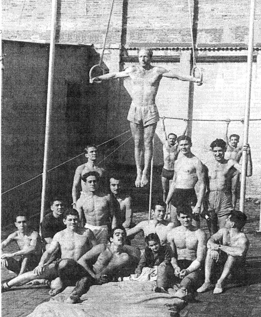 Fritz Lehmann, entrenador de la Federació Catalana de Gimnàstica artística efectuant un Crist a les anelles de la terrassa de les instal·lacions del Barcelonès, any 1950. A baix, assegut al segon de la dreta, trobem a un jove Joaquim Blume que participava també els entrenaments.