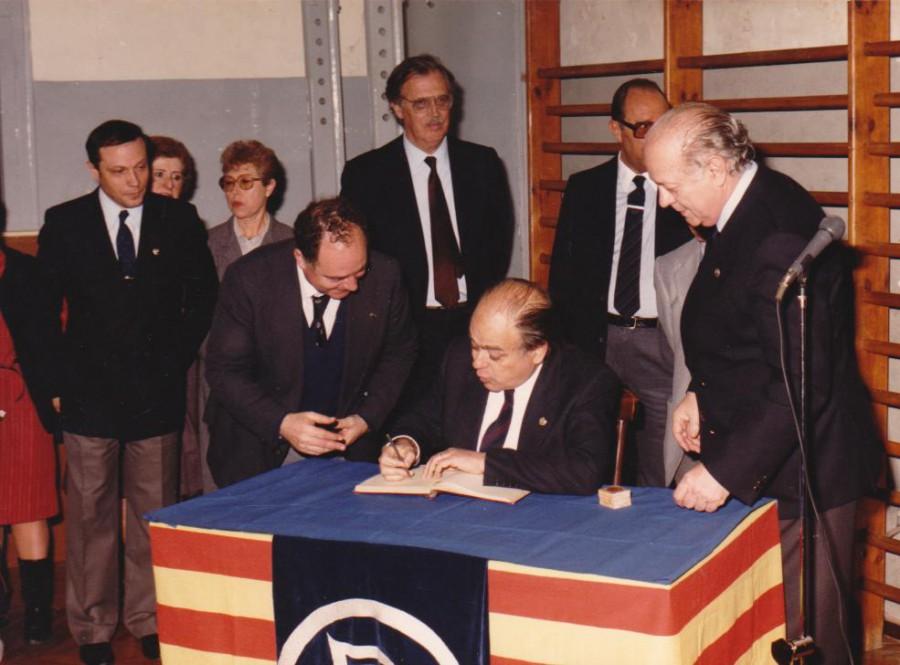 El President de la Generalitat en Jordi Pujol signant el Llibre d'Or del CGB sota l'atenta mirada d'en Lluís Aparicii altres membres de la Junta Directiva. Al fons trobem en Ramon Trias Fargas, Conseller d'economia i Finances de la Generalitat
