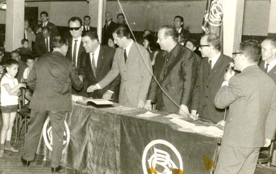 Vicens Calderón fent de presentador en el repartiment de medalles dels 25 anys de socis a la Sala Iris. El podem veure amb el micròfon a la mà. A la foto: Mortes, Aparicio, G.Ros, J.M. Vidal, en el momnet del lliurement en a Gracià Cuesta. Any 1958.