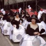 """Amb la disfressa """"Les pilotes la politica del poble"""" 2008 la comparssa desfilant per un carrer del Raval al so de trompetes i timbals."""